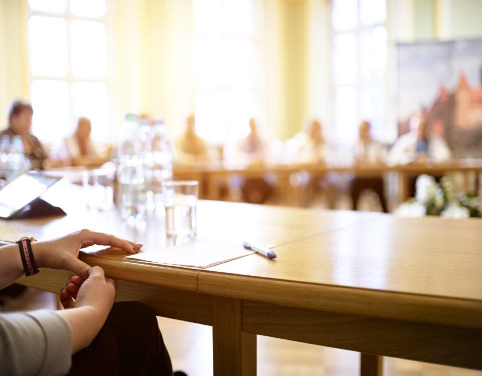Mehrere Menschen sprechen miteinander an einem runden Tisch